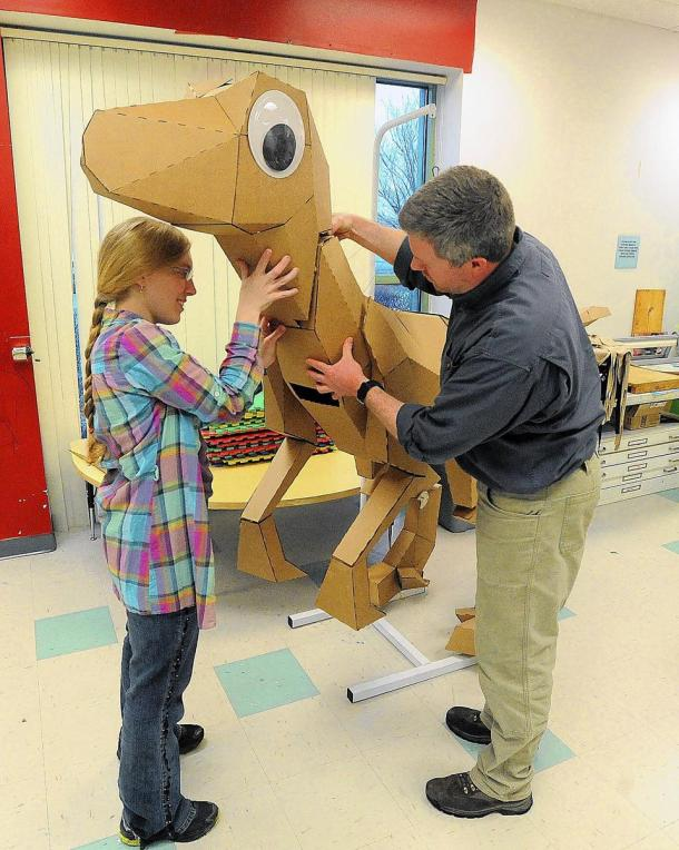 ( KEVIN MINGORA, THE MORNING CALL / April 3, 2014 ) Making the dinosaur image caption: Lisa Glover, a Lehigh University grad student, and technical entrepreneurship professor Brian Slocum put together Felix a 15-foot E-fluted corrugated fiberboard dinosaur that Glover created. Image source: The Morning Call newspaper